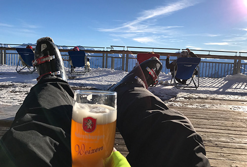 A skier drinking a weizen on a sunny chair at the Diedamskopf.