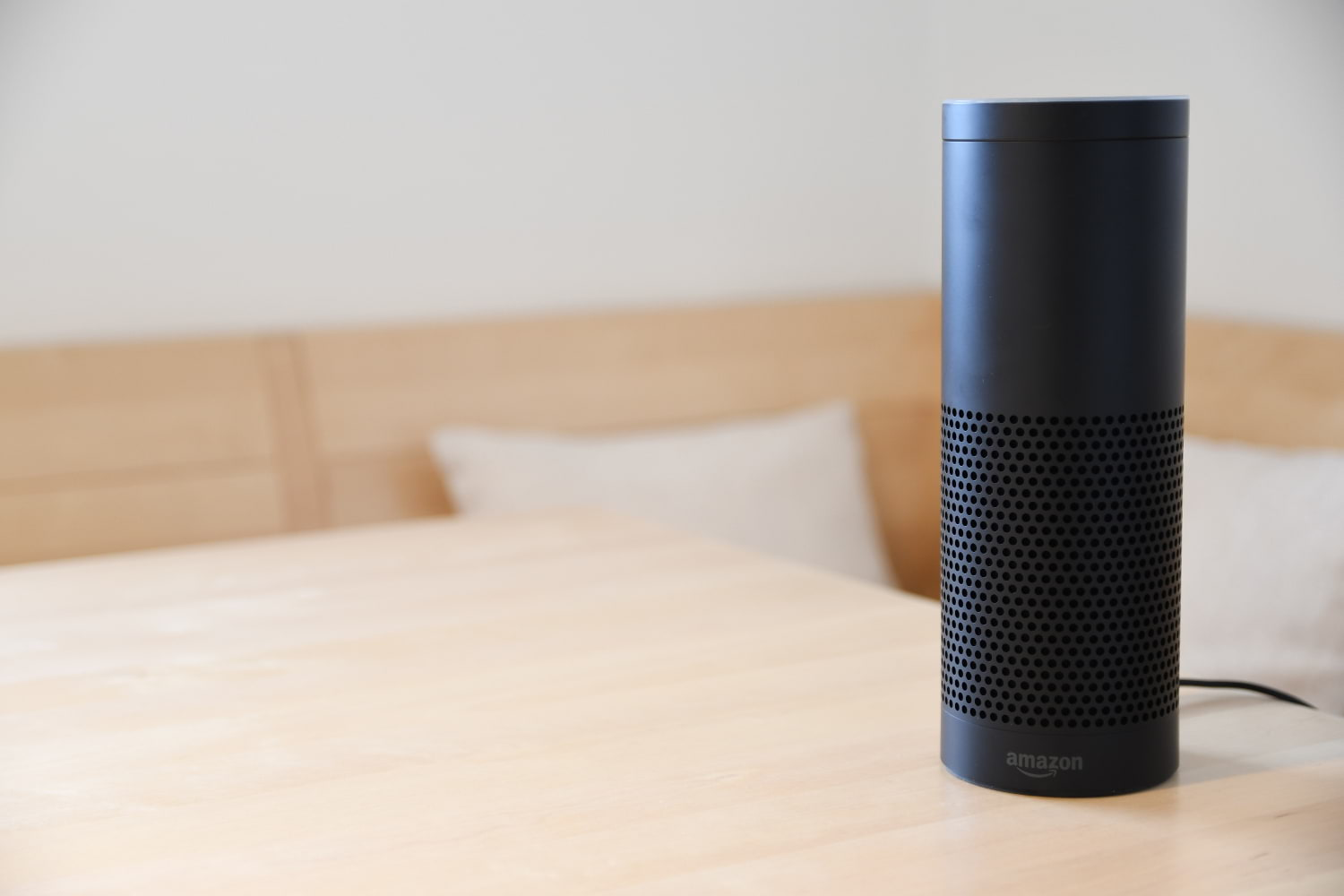 An Amazon Echo Plus on a wooden table in a bright environment.